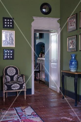 durchgang mit weiss lackierter holzverkleidung neben sessel und wandtisch vor bildersammlung an. Black Bedroom Furniture Sets. Home Design Ideas