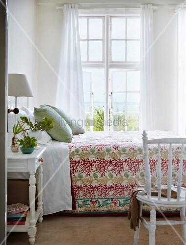blick durch offene t r auf bett mit komforth he und gebl mter tagesdecke vor sprossenfenster. Black Bedroom Furniture Sets. Home Design Ideas