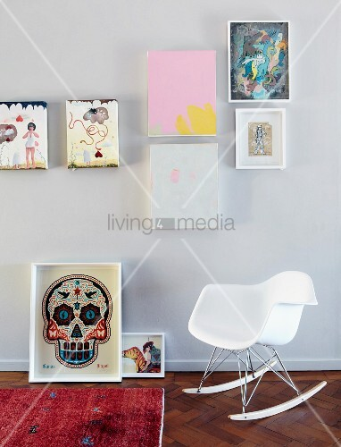 charles eames schaukelstuhl in weiss vor wand mit verschiedenen aufgeh ngten bildern am boden. Black Bedroom Furniture Sets. Home Design Ideas