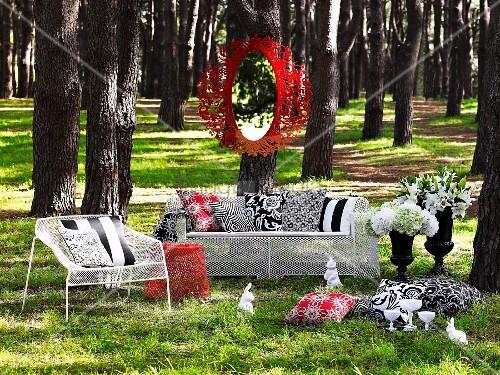 spiegel mit rotem metallrahmen an baum aufgeh ngt weisse outdoor m bel aus maschendraht mit. Black Bedroom Furniture Sets. Home Design Ideas