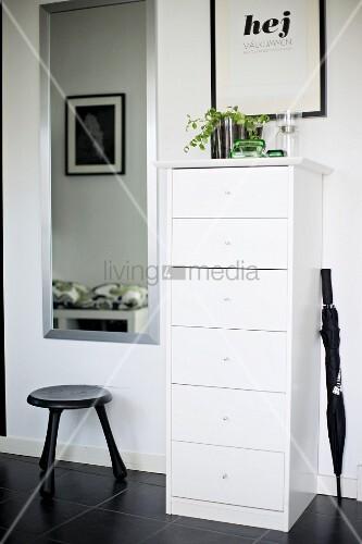 schmaler weisser kommodenschrank und schwarzer schirm. Black Bedroom Furniture Sets. Home Design Ideas