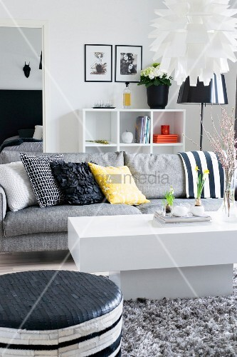 White coffee table in front of grey sofa with colourful