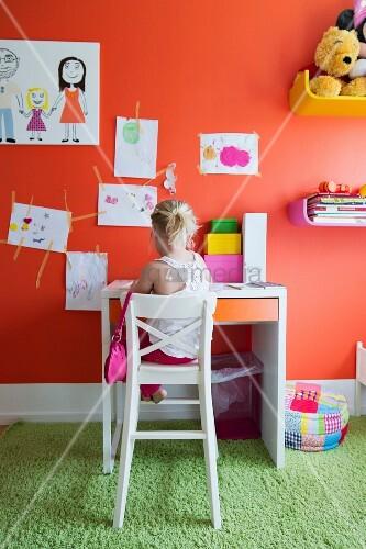 ausschnitt eines farbigen kinderzimmers kind auf hohem weissem stuhl vor schreibtisch an. Black Bedroom Furniture Sets. Home Design Ideas