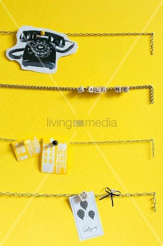 Gliederketten auf gelber Wand als Pinnwand – living4media
