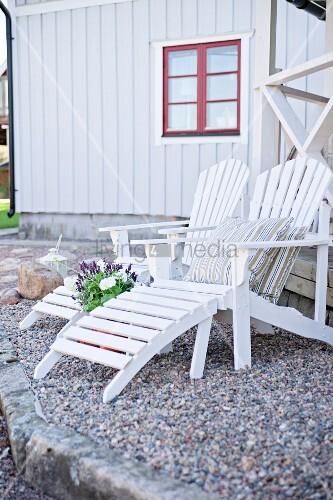 weisse holz liegest hle auf gekiestem terrassenboden im hintergrund holzhaus mit rotem fenster. Black Bedroom Furniture Sets. Home Design Ideas