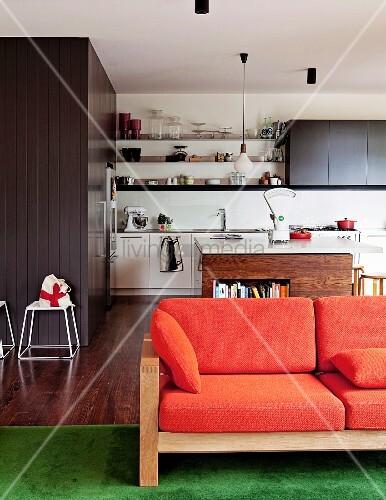 sofa mit holzgestell und orangefarbenen polstern vor der offenen k che einbauten hinter grauer. Black Bedroom Furniture Sets. Home Design Ideas