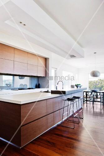 designerk che in lichtdurchflutetem wohnraum lange theke mit holzfront und aufgesetzter platte. Black Bedroom Furniture Sets. Home Design Ideas