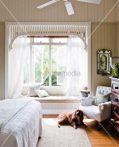 hund vor einem polstersessel im schlafzimmer romantischer fenstererker mit gardinen und. Black Bedroom Furniture Sets. Home Design Ideas