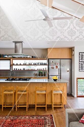 offener wohnraum mit modernem k chenbereich theke und barhocker aus holz bild kaufen. Black Bedroom Furniture Sets. Home Design Ideas