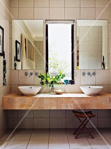 moderner waschtisch mit zwei aufsatzbecken auf platte vor gefliester wand mit spiegeln neben. Black Bedroom Furniture Sets. Home Design Ideas