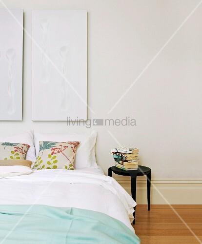 weisses diptychon ber doppelbett mit floral gemusterten. Black Bedroom Furniture Sets. Home Design Ideas