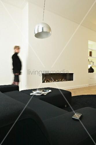 weisses wohnzimmer mit schwarzer sofagarnitur und einbaukamin bild kaufen living4media. Black Bedroom Furniture Sets. Home Design Ideas