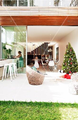 weihnachtsbaum auf sonniger terrasse vor offener glas schiebet r und blick in wohnraum auf. Black Bedroom Furniture Sets. Home Design Ideas