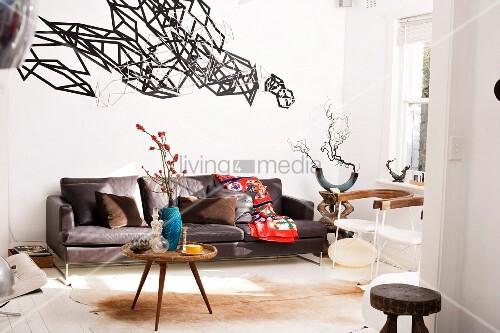ledersofa in wohnraum mit accessoires im ethnostil. Black Bedroom Furniture Sets. Home Design Ideas