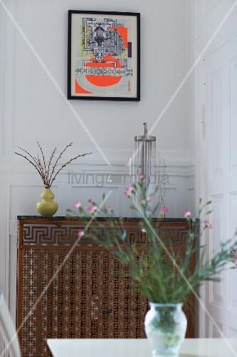 vase mit blumen auf tisch vor heizk rper mit metallverkledung bild kaufen living4media. Black Bedroom Furniture Sets. Home Design Ideas
