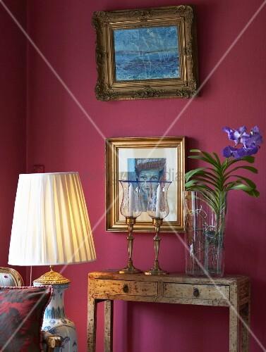 vintage konsolentischchen mit vase und blumenzweig neben kerzenhaltern vor weinroter wand mit. Black Bedroom Furniture Sets. Home Design Ideas