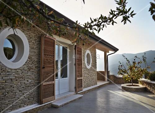 mediterranes wohnhaus mit bullaugenfenster und terrassent r mit t rl den aus holzlamellen bild. Black Bedroom Furniture Sets. Home Design Ideas