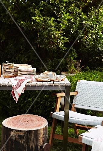 gedeckter tisch mit baumstamm als hocker und weisser stuhl im garten bild kaufen living4media. Black Bedroom Furniture Sets. Home Design Ideas