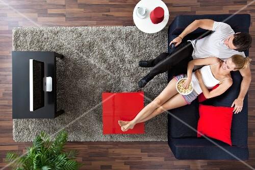 Fr Hliches Paar Sitz Mit Popcorn Auf Dem Sofa Vor Dem Fernseher Im Wohnzimmer Bild Kaufen