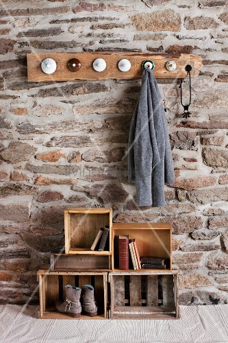 Nice Rustic DIY Cloakroom In Room With Stone Wall; Coat Pegs Made From Old China  Lids And Old Wooden Crates On Floor As Storage