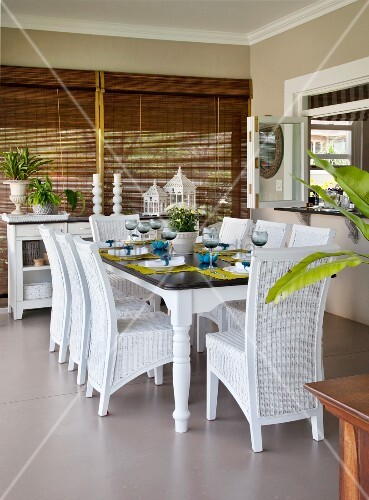 weisse rattanst hle um gedeckten tisch in der loggia im. Black Bedroom Furniture Sets. Home Design Ideas