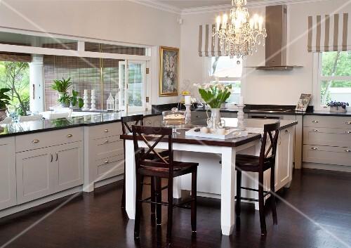 esstisch und dunkle holzst hle vor theke in der k che mit. Black Bedroom Furniture Sets. Home Design Ideas
