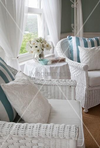 weiss lackierte rattansessel mit kissen und runder beistelltisch mit weisser blumenstrauss vor. Black Bedroom Furniture Sets. Home Design Ideas