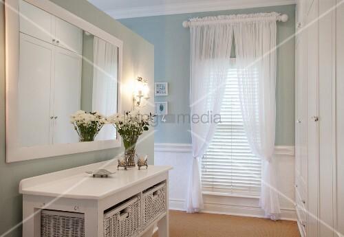 konsolentisch mit weissen rattankisten vor wandspiegel im hintergrund drapierte vorh nge am. Black Bedroom Furniture Sets. Home Design Ideas