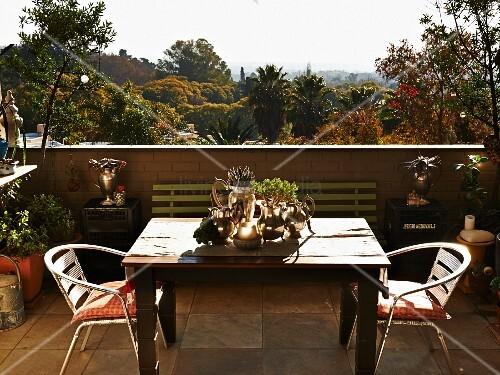 Terrasse mit holztisch und metallst hlen blick ber tropische landschaft bild kaufen - Holztisch terrasse ...