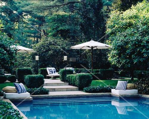 gartenanlage mit ruhepl tzen unter sonnenschirmen und pool bild kaufen living4media. Black Bedroom Furniture Sets. Home Design Ideas