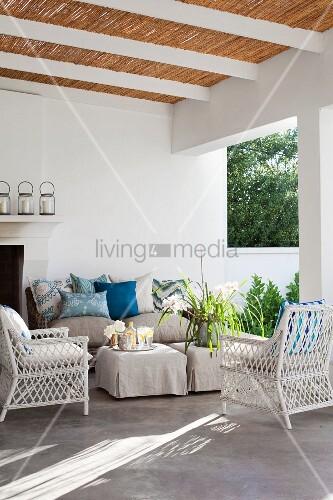 weisse rattansessel und beistelltische mit hussen vor. Black Bedroom Furniture Sets. Home Design Ideas