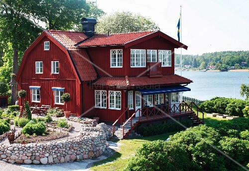schwedisches historisches holzhaus mit roter fassade in park hnlichem garten am meer bild. Black Bedroom Furniture Sets. Home Design Ideas