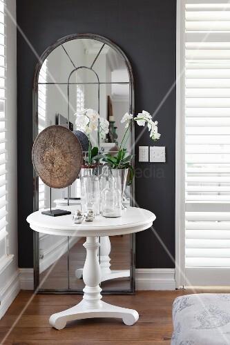 weisser runder beistelltisch mit orchideen vor standspiegel mit rundbogen an dunkler wand. Black Bedroom Furniture Sets. Home Design Ideas
