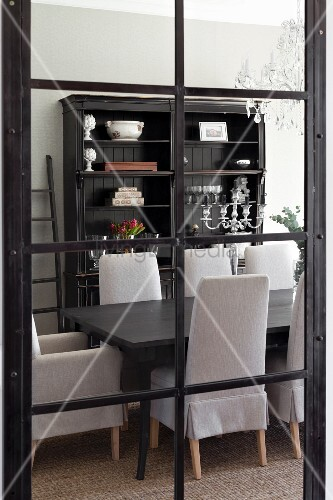 blick durch fenstert r mit schwarzen metallsprossen auf esstisch aus dunklem holz und st hle. Black Bedroom Furniture Sets. Home Design Ideas