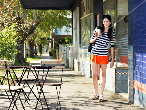 junge frau mit kaffeebecher zum mitnehmen im stra encafe bild kaufen living4media. Black Bedroom Furniture Sets. Home Design Ideas