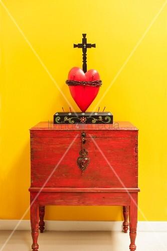 Kruzifix über rotem Herz auf Schränkchen vor leuchtend ...