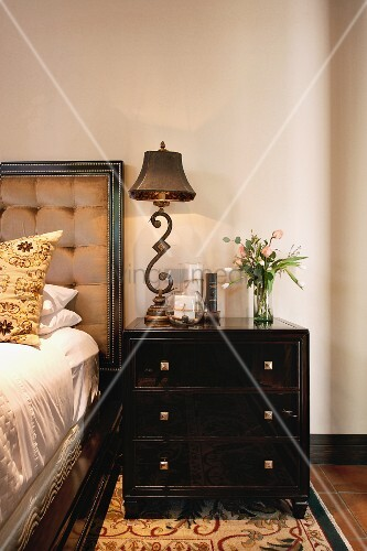 kommode als nachttisch neben bett mit antiker tischleuchte bild kaufen living4media. Black Bedroom Furniture Sets. Home Design Ideas