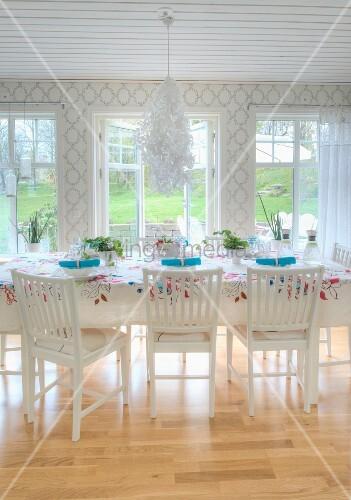 bl ten kronleuchter ber festlich gedecktem esstisch mit floral gemusterter decke im weissen. Black Bedroom Furniture Sets. Home Design Ideas