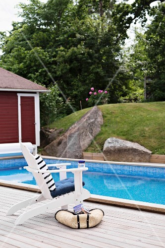 weisser stuhl auf holzterrasse an pool mit gartenblick bild kaufen living4media. Black Bedroom Furniture Sets. Home Design Ideas