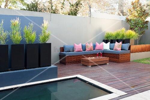 eingelassenes wasserbecken in modern gestaltetem patio sitzbank mit kissen und schwarze. Black Bedroom Furniture Sets. Home Design Ideas