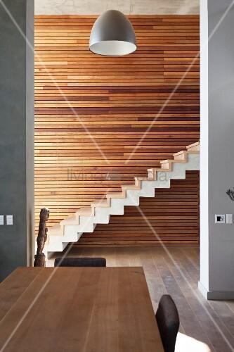 essplatz vor raumhohen durchgang und blick auf minimalistische treppe mit holzstufen auf. Black Bedroom Furniture Sets. Home Design Ideas