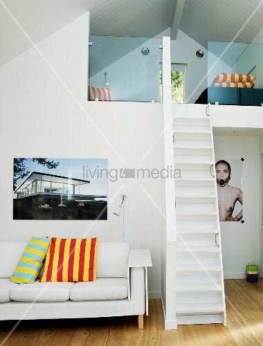 schmale steile treppe zur galerie unterm dach daneben weisse couch mit streifenkissen und. Black Bedroom Furniture Sets. Home Design Ideas