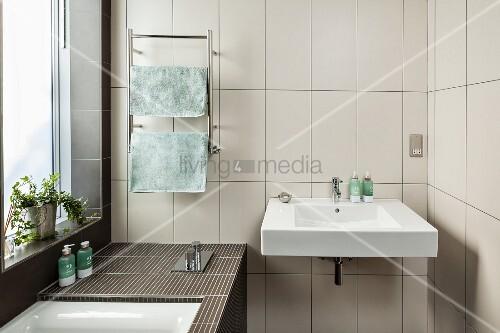 waschbecken an wand mit weissen hochformatigen fliesen seitlich eingebaute badewanne am. Black Bedroom Furniture Sets. Home Design Ideas