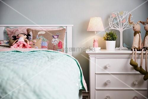 m dchenzimmer stoffpuppe auf besticktem kissen im bett mit kopfteil neben weisser kommode mit. Black Bedroom Furniture Sets. Home Design Ideas
