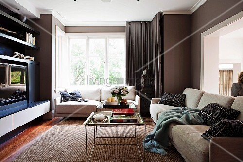 Filigrane Beistelltische Und Gemtliches Polstersofa Gegenber Wandschrank Im Hintergrund Sofa Vor Fenster Mit Bodenlangen Dunklen Vorhngen In Wohnzimmer