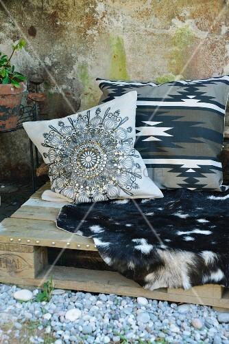 sitzplatz aus alter holzpalette mit ziegenfell und kissen im ethno look bild kaufen living4media. Black Bedroom Furniture Sets. Home Design Ideas