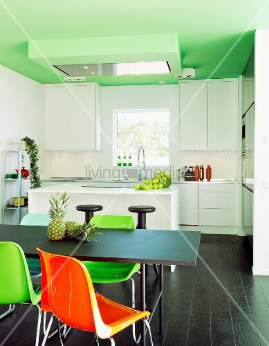 farbige kunststoff st hle an schwarzem tisch und dunkler. Black Bedroom Furniture Sets. Home Design Ideas