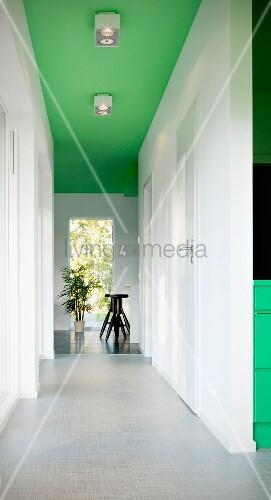lichtdurchfluteter weisser gang mit hellgrauem boden im hintergrund schwarze barhocker gr n. Black Bedroom Furniture Sets. Home Design Ideas