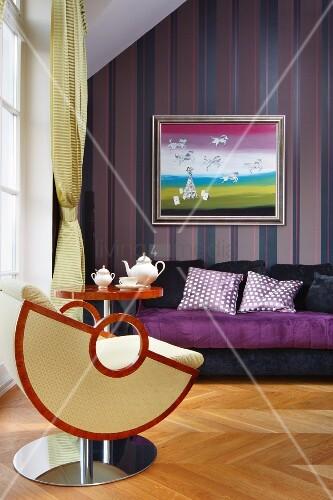 designersessel und beistelltisch vor lila sofa und bild an. Black Bedroom Furniture Sets. Home Design Ideas