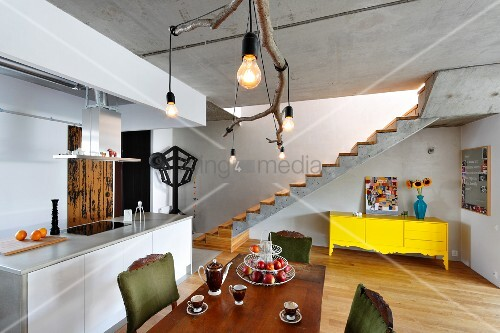 Rustikale Ast Leuchteüber Esstisch neben Kücheninsel; gelbe Kommode unter Sichtbetontreppe im